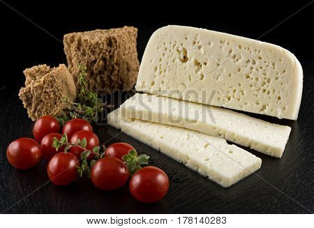 Slices of traditional sfella cheese of Peloponnese, Greece, on black tray with little tomatoes, rusk and oregano