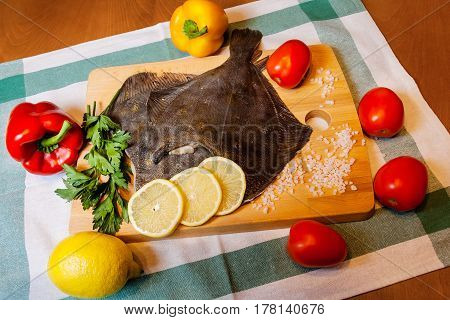 Fresh raw flounder and vegetables on cutting board