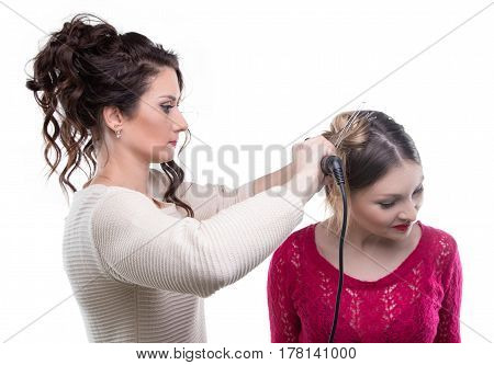 Working hairdresser curling client on white background