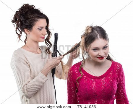 Working hairstylist curling client on white background
