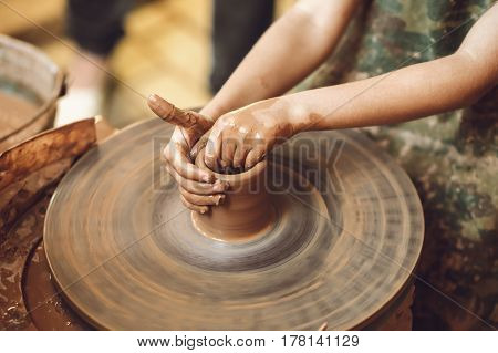 Child making pot of clay on potter's wheel process of sculpting from clay