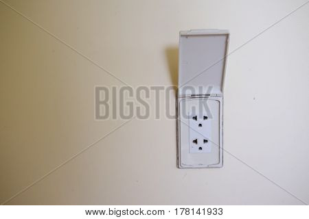 Electric plug outlet on white wall at home