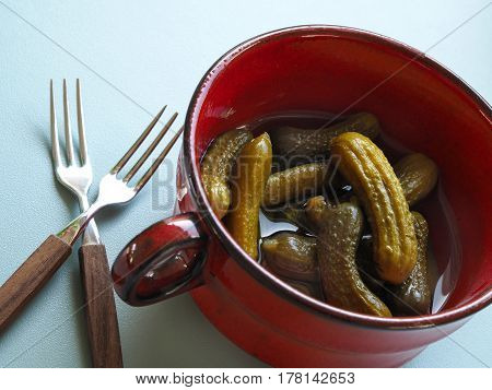 Gherkins in a rustic red ceramic bowl on a modern kitchen table