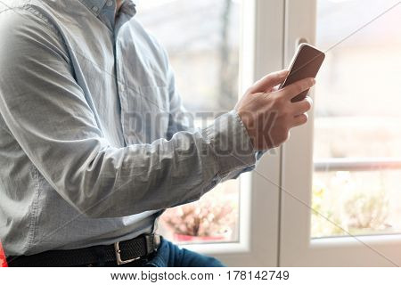Man Using His Mobile Phone At Home
