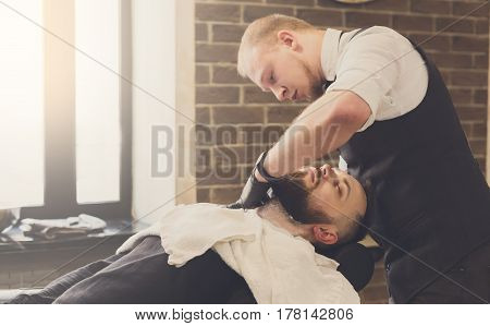 Barber styling beard to client at barbershop. Stylish hairdresser in male hair salon
