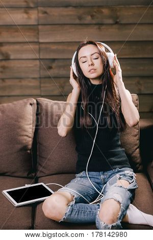 Young beautiful brunete girl with white headphones and tablet sitting on brown sofa and listening favorite music on wooden background
