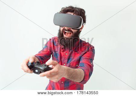 Cheerful man playing the game in virtual reality helmet. Horizontal studio shot.
