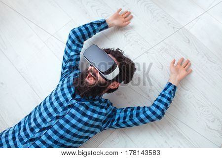 Cheerful man wearing the virtual reality goggles lying on the floor from above.