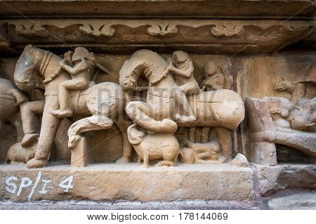 Procession Of Indian People And Horses On Stone Textures Wall Of Khajuraho Temple, India.