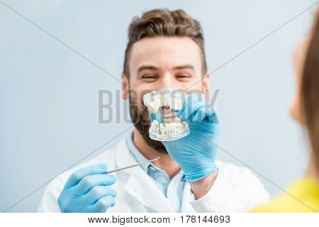 Handsome dentist consulting woman patient holding artificial jaw at the dental office