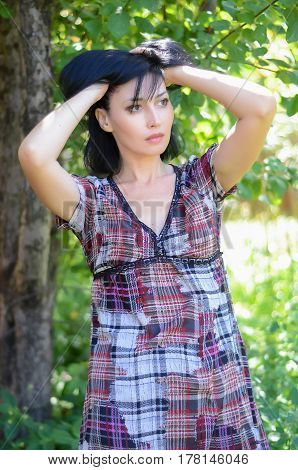 Young brunette woman in a plain gingham dress in a garden holding her head