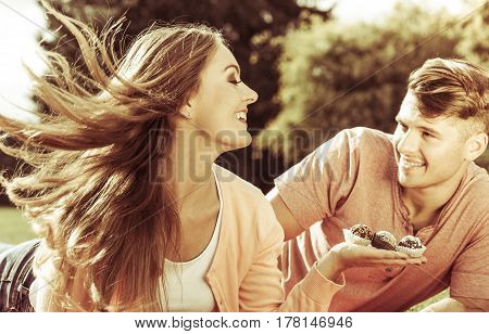 Love and dating. Attractive woman giving cupcakes cookies to handsome man. Happy cute lovers on date outdoor.