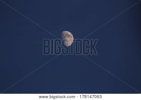 A waxing gibbous moon on a light evening