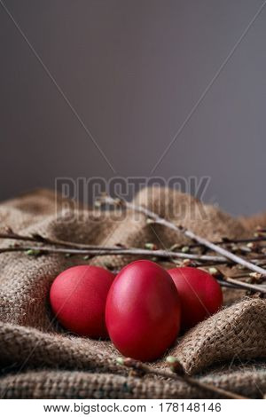 Three Easter eggs spring branches on a bag material on an old wooden table