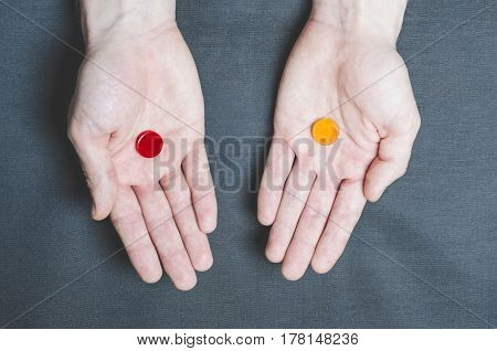 Two Tablets Red And Yellow In Different Hands, Choice