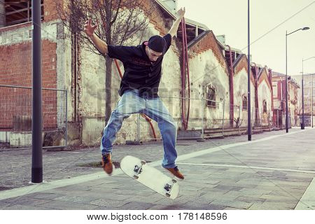 Young Boy Jumping With Skateboard In Outskirt Street