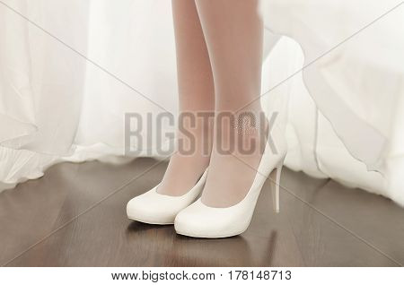 Graceful legs of the bride in white shoes on a high heel