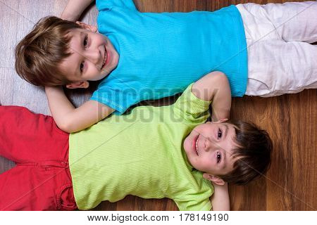 Happy Kids Relaxing Laying On Floor- Top View