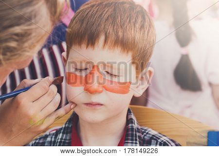 Child with funny face art painting. Painter makes tiger eyes on boy's face. Children holiday, birthday party entertainment.