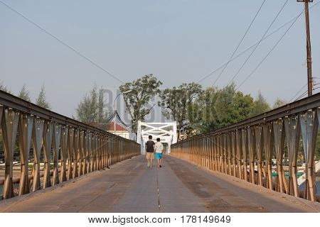 the backs of two children walking away across a metal river crossing bridge in Cambodia.