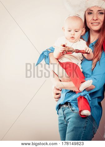 Family celebration concept. Christmas woman with cute baby. Beautiful lady has red santa claus cap.