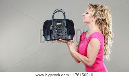 Love to shopping. Satisfaction from buying new fashionable accessories and clothes. Elegant woman with purchase. Female in pink with navy blue bag.