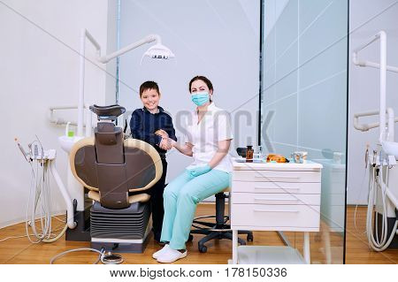 Doctor dentist and child handshake in the office. Dental treatment.