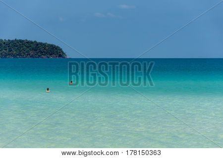 Two people in a crystal clear calm tropical sea with headland on the horizon.