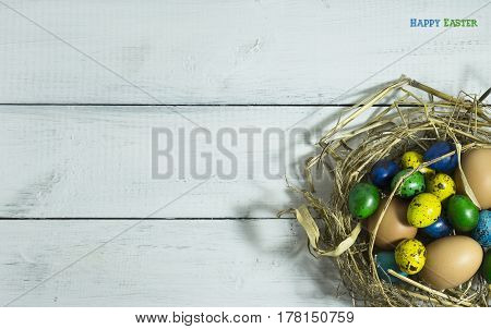 Easter colorfull eggs in a nest on a white wooden background with copy space