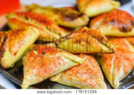Cooked patties lie on a metal plate sprinkled with red spices