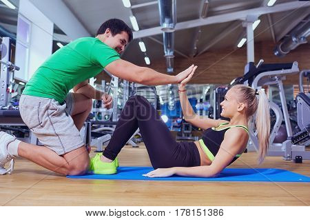 Sport girl doing abs exercises with a trainer man on the floor at the gym.