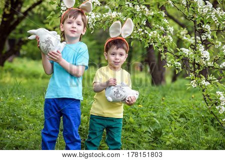 Two little kids boys and friends in Easter bunny ears during traditional egg hunt in spring garden outdoors. Siblings having fun with finding colorful eggs. Old christian and catholoc tradition.