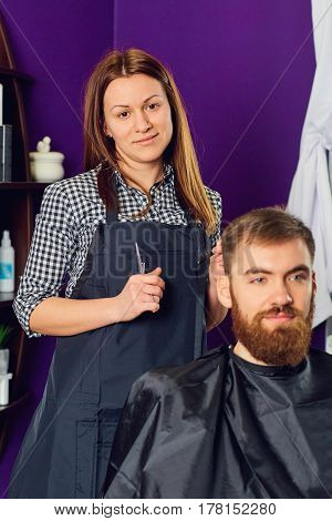 Portrait of a female hairdresser in  beauty salon indoors.