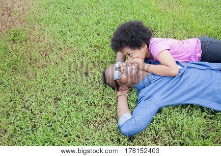 African American Father And Little Kid Whispering And Gossiping With Trust On Green Grass - With Cop