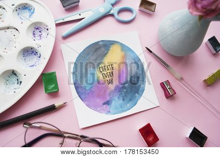 Artist workspace. Inspirational quote create every day palette watercolor brush glasses Flat lay