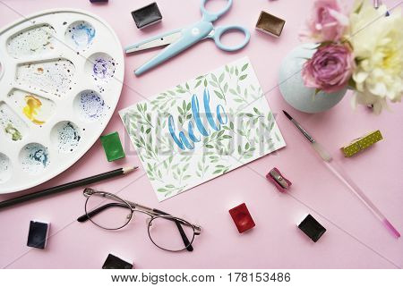 Artist workspace. Hello written in calligraphy style palette watercolor brush glasses scissors bouquet of flowers on a pink background. Flat lay.