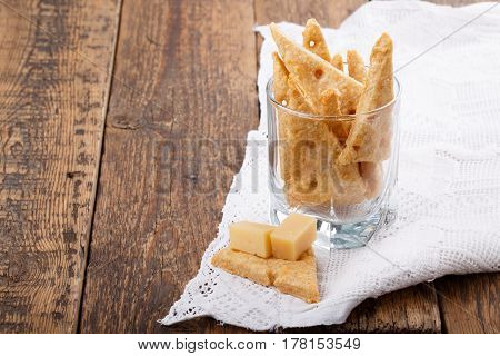 Homemade cheesy crackers shaped as slices of cheese. Perfect crispy snack. Copy space.