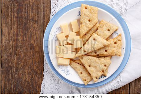 Homemade cheesy crackers shaped as slices of cheese. Perfect crispy snack. Top view. Copy space.