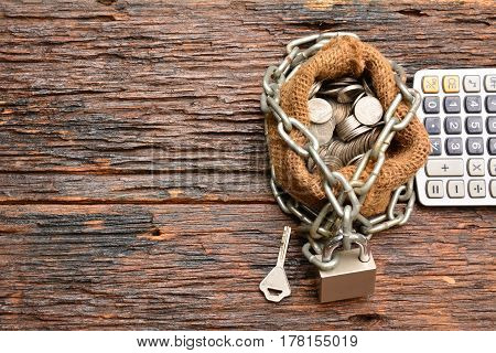 coins with chain with key with calculator and sack bag on with wooden background for business and financial concept.