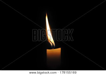 Close-up of a burning candle on a black background.