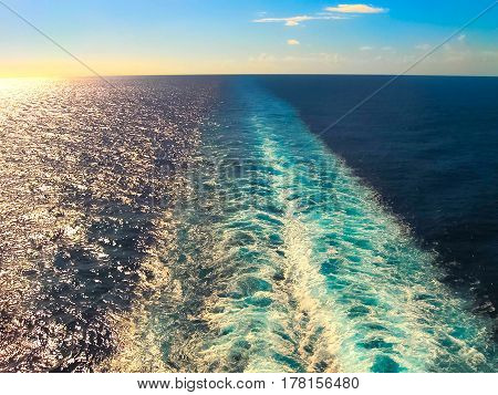 The foam on the blue water of sea at sunset