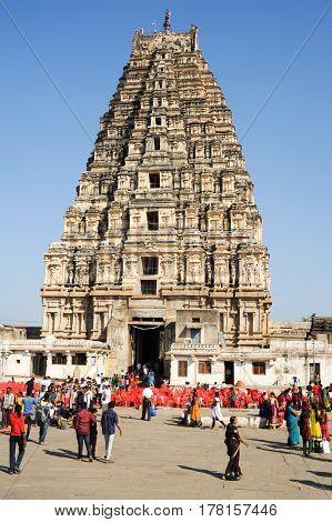 Hampi India - 11 January 2015: People walking in front of View of Shiva-Virupaksha Temple located in the ruins of ancient city Vijayanagar at Hampi India