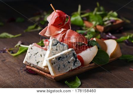 Blue Cheese With Prosciutto And Pear On A Wooden Table