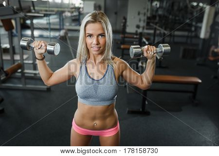 Sexy Beautiful Athletic Woman Pumping Up Muscules With Dumbbells In Gym