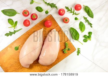 Chicken fillets with cherry tomatoes, fresh herbs including basil leaves, corn salad, and ruccola, shot from above on a cutting board, with a place for text