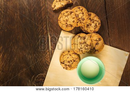 An overhead photo of chocolate chips cookies on baking paper, with a glass of milk, and copy space
