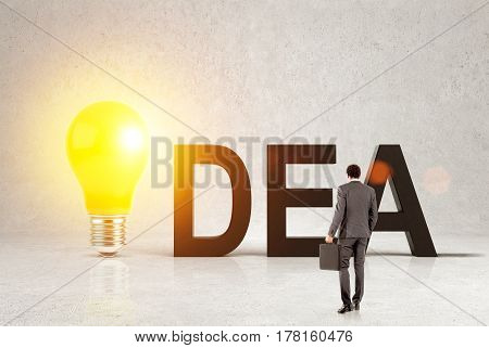 Rear view of a businessman with a suitcase looking at a large idea word. The letter i is a light bulb