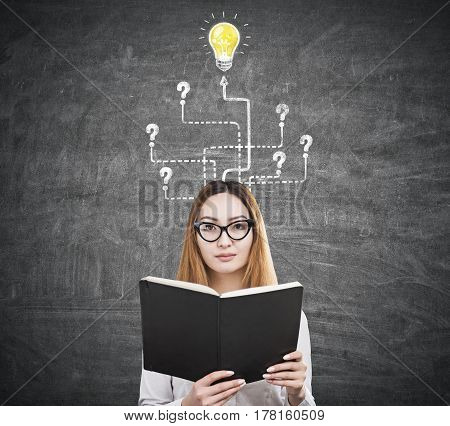 Portrait of an Asian businesswoman wearing glasses and reading a book while standing near a blackboard with a light bulb sketch and question marks.