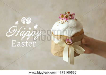Text HAPPY EASTER and female hand holding traditional cake on light background