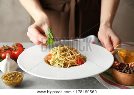 Woman decorating tasty pasta with basil leaves